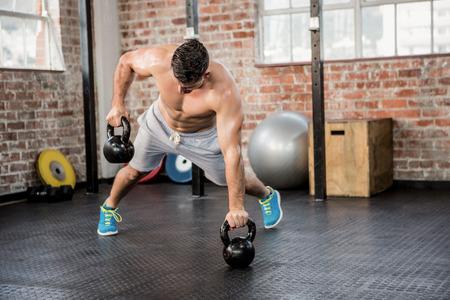 Photo for Shirtless man lifting kettlebell at the gym - Royalty Free Image