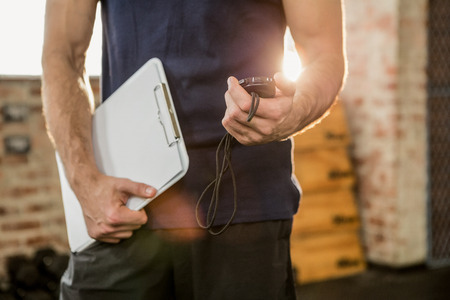 Foto de Midsection of trainer holding clipboard and stopwatch at the gym - Imagen libre de derechos