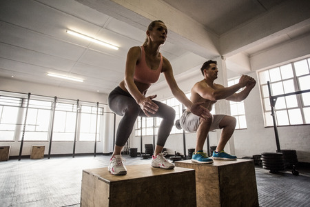 Photo pour Muscular couple doing jumping squats in crossfit gym - image libre de droit