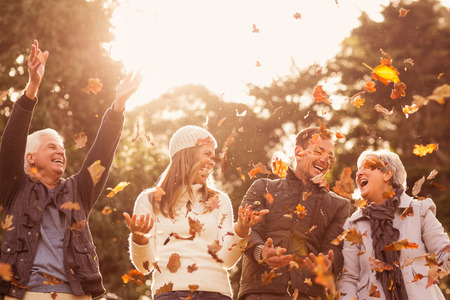 Foto de Happy family throwing leaves around on an autumns day - Imagen libre de derechos