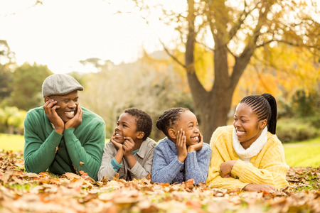 Portrait of a young smiling family lying in leaves on an autumns day