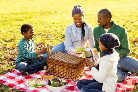 Photo pour Young smiling family doing a picnic on an autumns day - image libre de droit