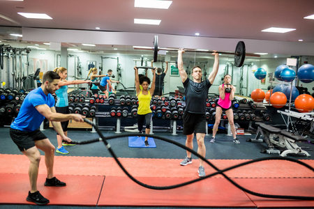 Foto de Fit people working out in weights room at the gym - Imagen libre de derechos