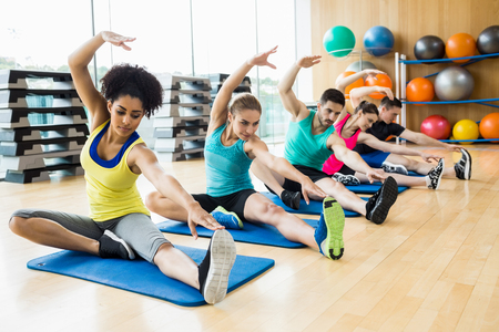 Photo pour Fitness class exercising in the studio at the gym - image libre de droit