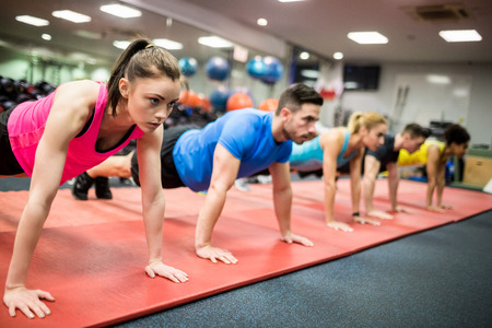 Photo for Fit people working out in fitness class at the gym - Royalty Free Image