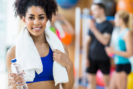 Photo for Fit woman smiling at camera at the gym - Royalty Free Image