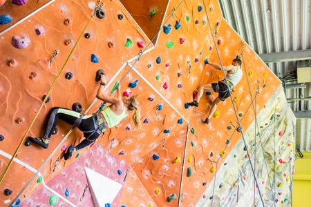 Foto de Fit couple rock climbing indoors at the gym - Imagen libre de derechos