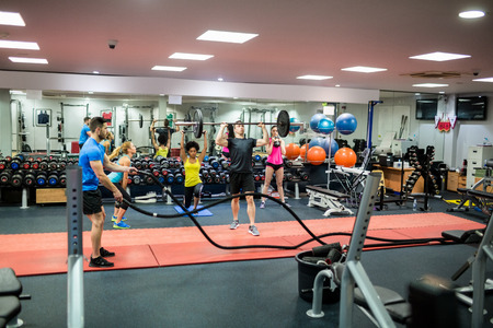 Photo pour Fit people working out in weights room at the gym - image libre de droit