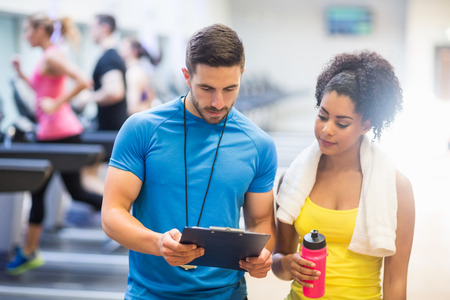 Foto de Fit woman talking to her trainer at the gym - Imagen libre de derechos