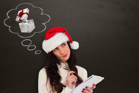Foto de Festive brunette thinking about her christmas list against blackboard - Imagen libre de derechos
