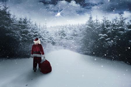 Photo pour Santa carrying sack of gifts  against snow scene - image libre de droit