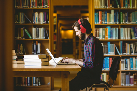 Foto de Hipster student studying in library at the university - Imagen libre de derechos