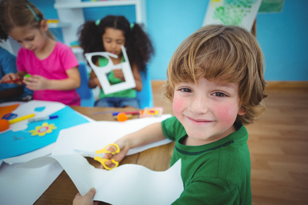Photo pour Happy kids doing arts and crafts together at their desk - image libre de droit