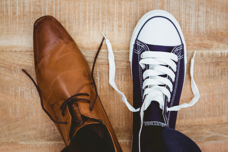 Photo pour View of two different shoes on wood plank - image libre de droit