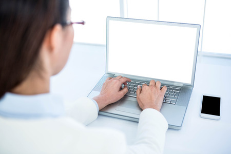 Photo for Rear view of businesswoman using laptop at the desk in work - Royalty Free Image