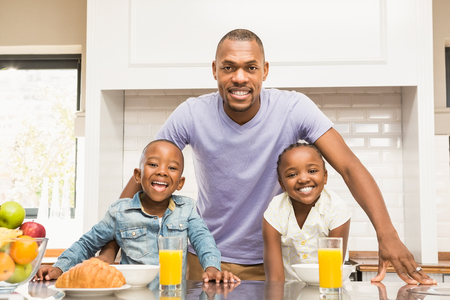 Photo pour Casual happy family having breakfast in the kitchen - image libre de droit