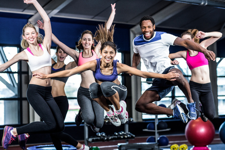 Photo pour Fit group smiling and jumping in gym - image libre de droit
