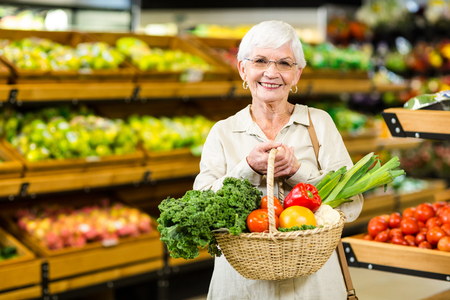 Photo for Senior woman holding wicker basket in supermarket - Royalty Free Image