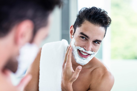 Photo for Handsome man shaving his beard in bathroom - Royalty Free Image