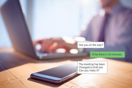Smartphone text messaging  against businessman using laptop at desk