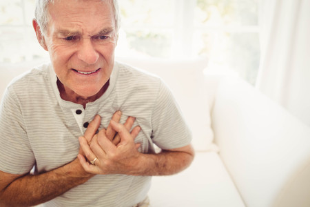 Foto de Senior man with pain on heart in bedroom - Imagen libre de derechos