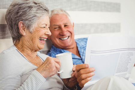 Photo pour Senior couple laughing while reading newspaper in bedroom - image libre de droit
