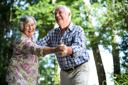 Photo pour Happy senior woman dancing with husband against trees in back yard - image libre de droit