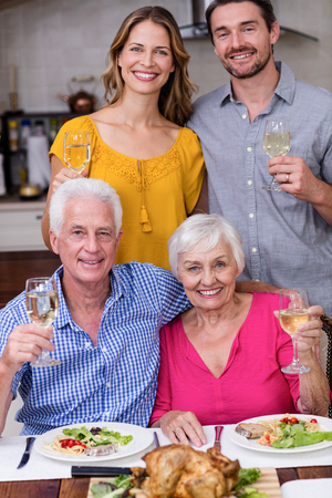 Portrait of a two generation family posing with a glass of wine near the dinner table