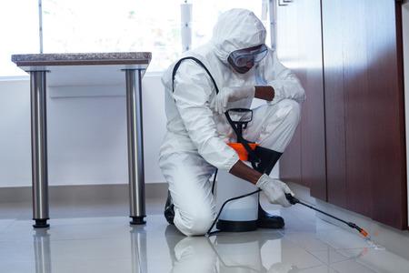 Photo pour Man doing pest control at home - image libre de droit