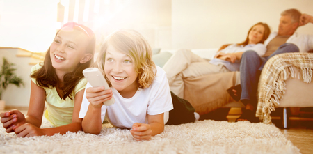 Photo pour Siblings lying on the floor watching tv together - image libre de droit