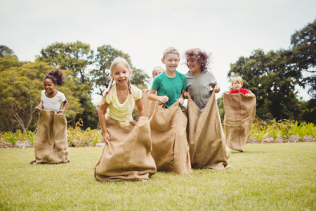 Photo for Children having a sack race in park on a sunny day - Royalty Free Image