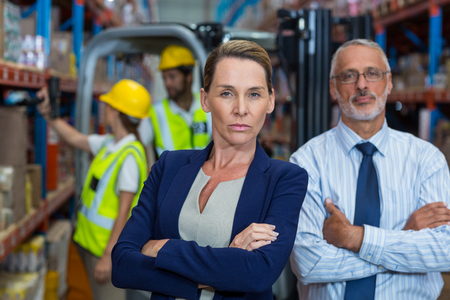 Photo for Serious managers are posing with crossed arms in warehouse - Royalty Free Image