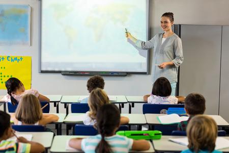 Foto de Female teacher teaching schoolchildren using projector screen in classroom - Imagen libre de derechos