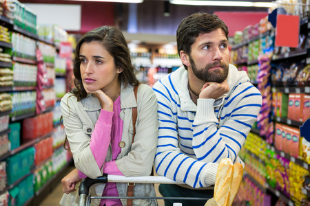 Foto de Bored couple with shopping trolley in organic section of supermarket - Imagen libre de derechos