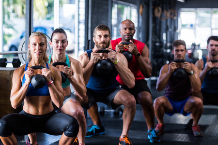 Photo pour Portrait of people holding kettlebells while crouching in gym - image libre de droit