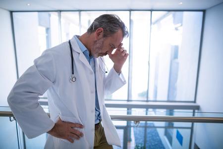 Photo pour Sad doctor standing in corridor of hospital - image libre de droit