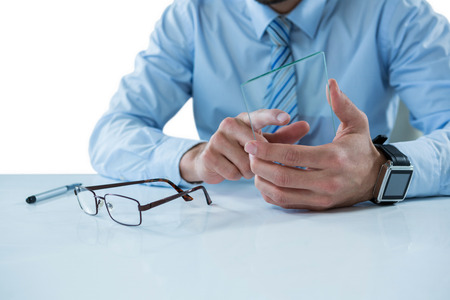 Mid section of businessman sitting at table touching a glass sheet