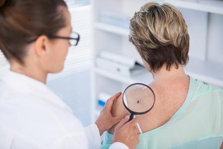 Foto de Dermatologist examining mole of female patient with magnifying glass in clinic - Imagen libre de derechos