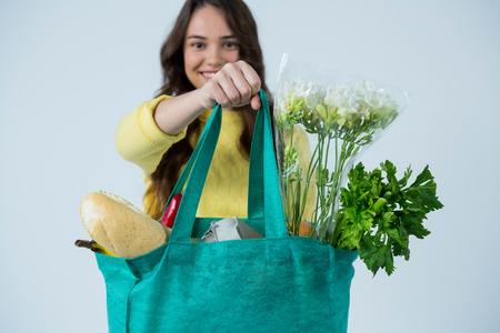 Photo for Portrait of beautiful woman carrying grocery bag against white background - Royalty Free Image
