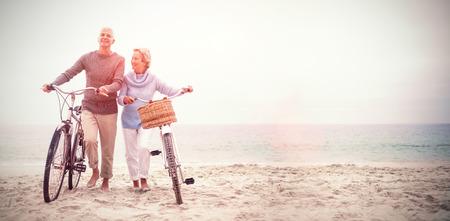 Foto de Full length of senior couple with their bicycles at the beach - Imagen libre de derechos