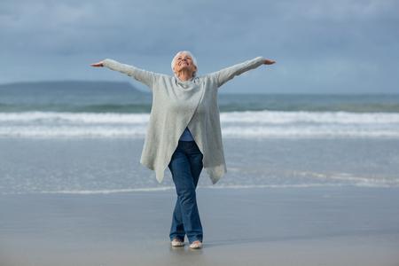 Photo pour Happy senior woman doing stretching exercise on the beach - image libre de droit