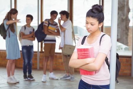 Foto de School friends bullying a sad girl in corridor at school - Imagen libre de derechos