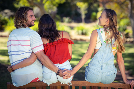 Photo for Rear view of man cheating on her woman in park - Royalty Free Image