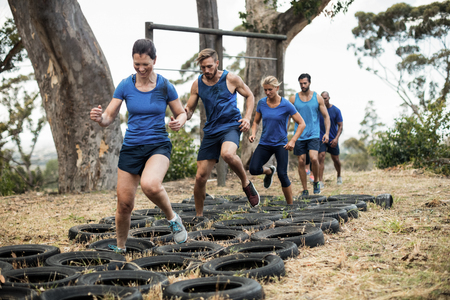 Photo for People receiving tire obstacle course training in boot camp - Royalty Free Image