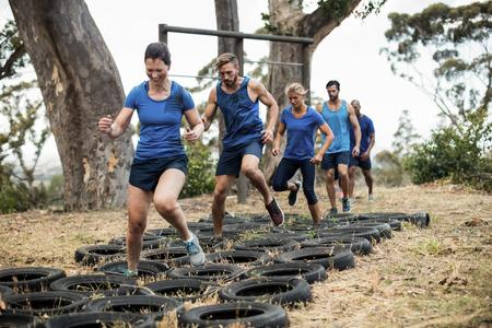 Foto de People receiving tire obstacle course training in boot camp - Imagen libre de derechos