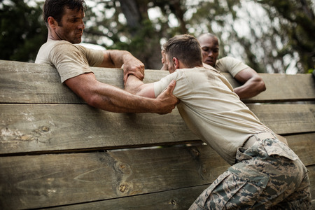 Foto de Soldiers helping man to climb wooden wall in boot camp - Imagen libre de derechos