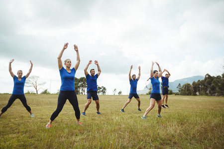 Photo for Fit people performing stretching exercise in bootcamp - Royalty Free Image