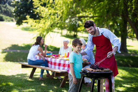 Photo for Father and son barbequing in the park during day - Royalty Free Image