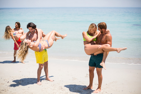 Photo for Men lifting women while standing on shore at beach during sunny day - Royalty Free Image