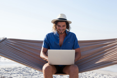 Photo for Smiling Man using laptop while sitting on hammock at beach during sunny day - Royalty Free Image